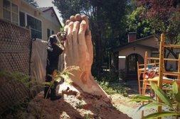 Mann fertigt mit Motorsäge große Menschenhand aus Holz