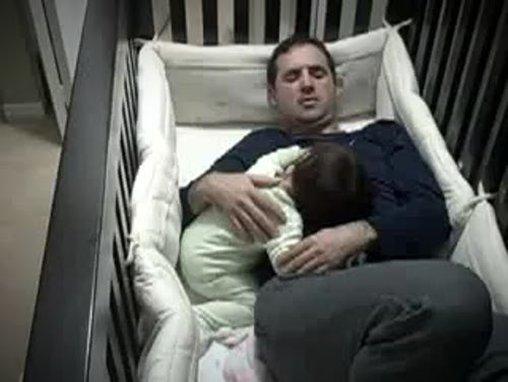 Papa schläft im Baby im Kinderbett